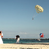 Newlyweds, with parasailer in the background.