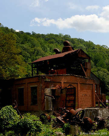 Here are the remains of the sawmill at Cass operated by the West Virginia Pulp and Paper (WVP&P).  Trees cut on the nearby mountains were brought here by the railroad to be processed into pulp or timber.  This structure is the planing mill with elevators to take wood to flooring machines some of which took 15 men to operate them.<br /> <br /> The logging operation here was originally set up to harvest red spruce which was excellent making pulp for fine papers.  Logging eventually expanded to the  hardwoods (oak, maple, cherry and birch) in this area.<br /> <br /> At its peak, 1922 to 1935, this mill ran two 11 hour shifts, six days per week processing about 125,000 board feet of lumber each shift.