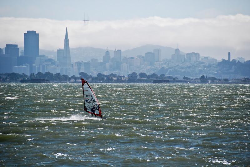 """<span id=""""title"""">Windsurfer</span> It was pretty windy out on the pier, but we got to see several windsurfers. I got a photo of this guy catching some pretty big air, but I chose to include this one for the background. I like how Sutro Tower is just peeking out of the fog."""