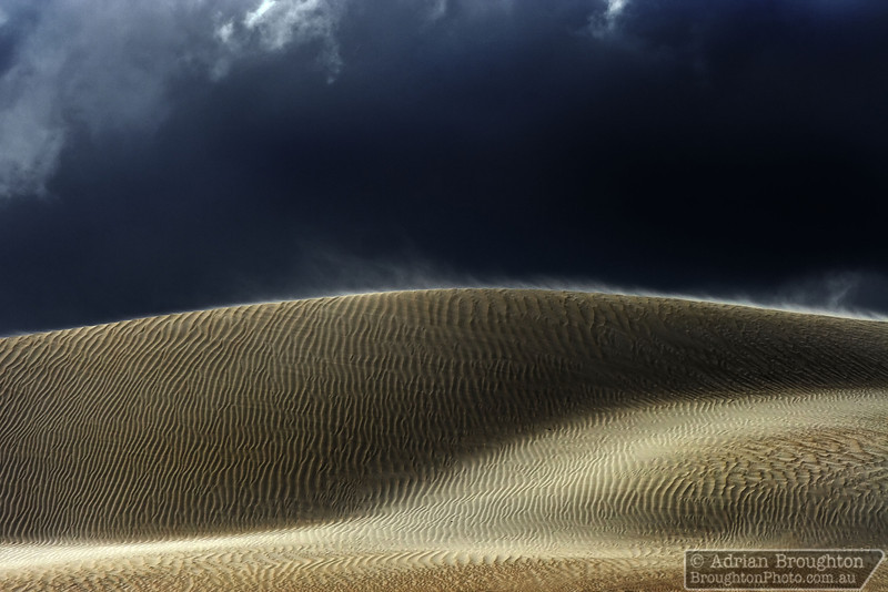 The wind whips up some sand across the top of the dunes.