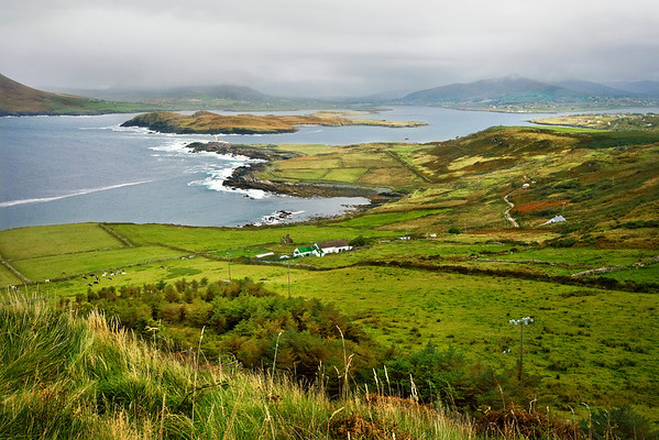 Valentia Island, a seven mile long island on the Iveragh Peninsula, County Kerry, is noted for its seascapes and rocky coastline, and for being the most westerly part of Europe. <br /> <br /> This view, from the north coast, captures Beginish Island in Doulus Bay, an inlet of Dingle Bay, as well as Doulus Head in the distance.<br /> <br /> Just barely visible on the tip of land is Cromwell Point Lighthouse.