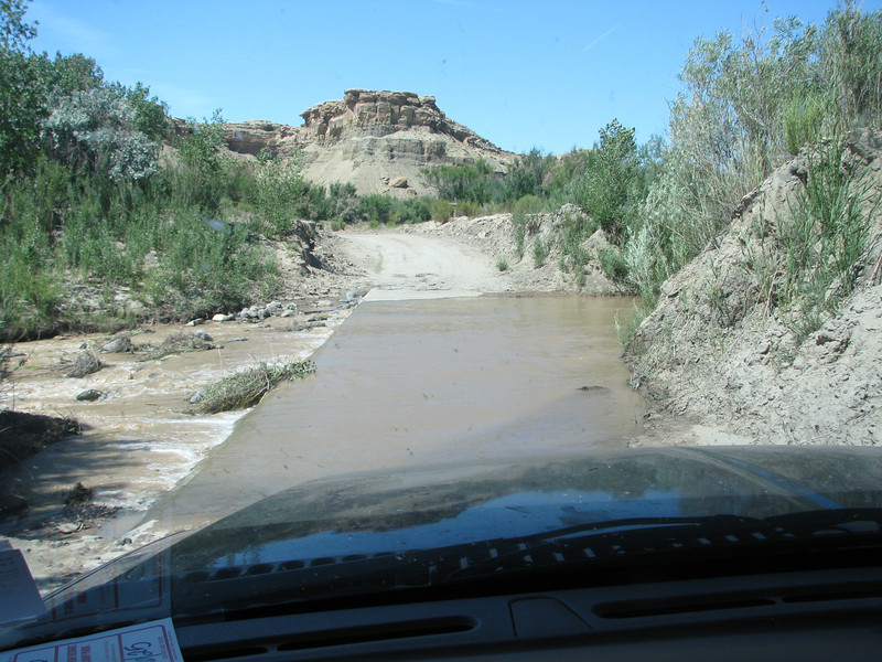 Fremont River crosses over a concrete road that has created a small dam.