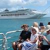 Tour boat sails around a cruise ship anchored at Whitsundays, Australia.