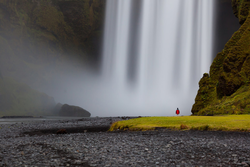 Man by a  Skógafoss waterfall