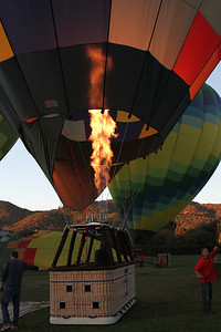 As the sunlight hits the nearby hills the balloons fill up.