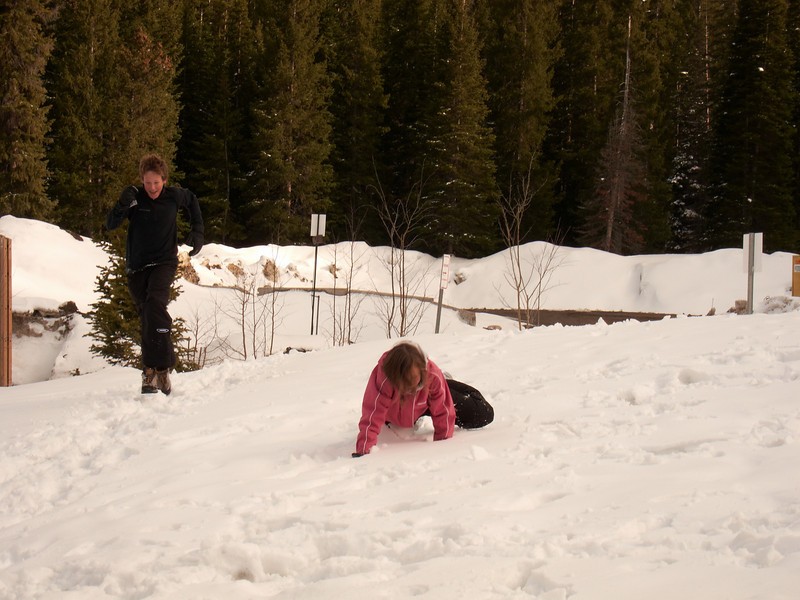 Josie falls deep into the snow at a critical point in a snow running race with Tyler