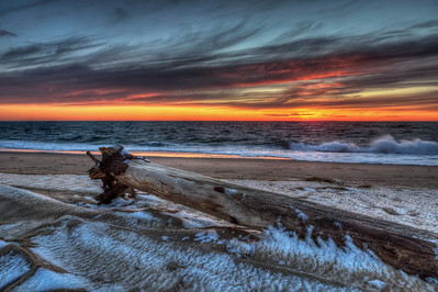 Oh, It Was So Windy!  Last year I was on a short visit to Boston and decided to drive to Cape Cod and see what is the buzz is all about. I grossly miscalculated timing and barely made to Provincetown to catch this sunset, arrived there maybe about ten minutes before it all ended. And it was oh so darn cold and windy, blowing from the west straight into my face. I took a few photos with my wide angle lens before it got sputtered by the wind with elements coming off the snow and the water. I had to get back to the car and change lenses to get the final shot. It was probably the shortest visit to Cape Cod seashore in its history.  To see the rest of the post visit Travel Photography by Dmitrii Lezine blog at http://sillymonkeyphoto.com