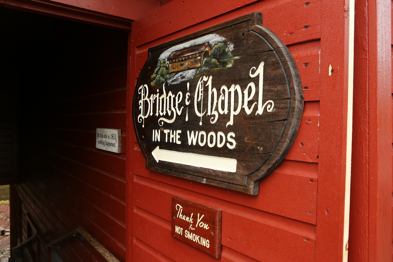 """Bridge & Chapel in the Woods.  Adjacent sign indicates that """"On this site in 1853 nothing happened."""""""