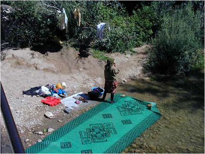 Here a Moroccan woman is doing the laundry. She has spread out a green rug on the bottom of the shallow stream and has hung the wet cloths on the bushes nearby to dry. A strange site for us but not an uncommon one.