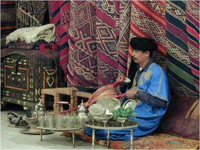 In Boumalne, we stopped in a rug shop and drank mint tea before discussing any business. Here the proprietor is making tea. It's a little difficult to see, but he is heating the water in a silver tea pot ...