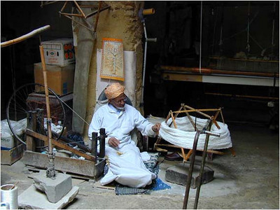 "Interestingly, many of these shops are models of ""vertical manufacturing integration."" In the same shop as above, an old man spins the thread used to weave the fabric. According to Islam, this man would leave his work 5 times a day to pray. Hence the prevalence of mosques within the  medina."