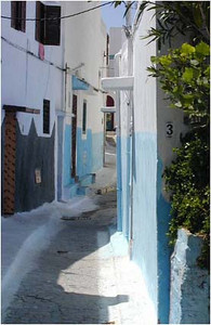 A narrow twisted street in Salé, Rabat's sister city. Many of the building of Morocco are painted white with light blue at street level. This is not entirely esthetic. The white reflects the sun and helps to control heat. The blue is said to discourage flies.