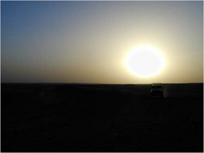 As we arrive at our camp, it is sunset. The sand and dust in the air turn the sun into a silver/gold ball of fire. Click the image at left to expand it (as usual) and you can just see the silhouette of our Land Rover, below and to the right of the sun.