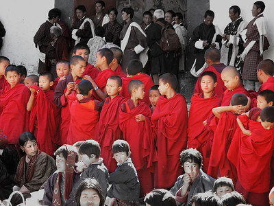 NRP Photo: My wife took this photo, arguably the best in the group. I did the selective desat in Photoshop. It shows a group of Monks attending the ceremony. Their red robes set them off as a group from the crowd just as their status of monks sets them off from the general population. This is life in Bhutan!
