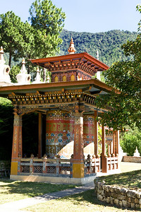 Two large prayer wheels are centered in the courtyard in front of the temple.