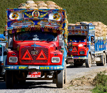 "(Almost) all the big ""Goods Carriers"" were similarly adorned. Check out the surrey-like fringe of sparkles, check out the eyes painted above the headlights, check out the paint job. Are these cool or what? Sometimes these trucks would be loaded with people ... and one of my favorites, we saw one full of monks going to a ceremony ... what I dubbed ""chock full of monks."""