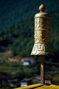 "As we arrive at the Chimi Lhakhang temple, we see this bell shaped adornment on top. All the temples we have seen have them.  This temple is dedicated to Drupka Kinley, one of Bhutan's favorite ""saints,"" known as ""the divine mad monk."" 500 years ago, this region was his stomping ground and this unconventional character taught Buddhist dharma using a shockingly ribald sense of humor. The landscape is dotted with evidence of his lasting influence (you'll see it in some of the pictures in this gallery) and villagers still tell stories of his exploits."