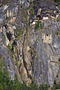 "The Tiger's nest has been built into the side of a 2,000 cliff. The ""cave"" I mentioned above is on the very right of the photo near the top. The ""retreat house"" is on the left mid-photo. You can just see the prayer flags spanning the chasm to the right of the monastery."