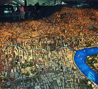 "Our last stop in Shanghai was unplanned, a whim really. We stopped in at the Urban Planning Exhibition. Inside was a scale model of the city of Shanghai. To my eye it was ""perfect."" By that I mean it featured an anatomically correct street map of Shanghai. Upon it were constructed model buildings that seemed to exactly resemble the real building we had been walking among. We could see the Bund, Pudong, the park across from our hotel and all the signature building we had been admiring. In fact, we could even see our hotel (circled in the second photo) and the street we walked down to a restaurant last evening. It was perfect!  I got to thinking, ""how do they keep it up to date?"" And then I began to notice the model had buildings that hadn't been built yet (the Expo site for example). And then it hit me; this wasn't modeled after the city; the city was being built based on the plan represented in the model ... hence the name, Urban Planning Exhibition! This is the power of a centrally planned economy and dictatorial rule. Hmm ... Another cultural whack on the side of the head ... one of many to come.  They have also built a 3D computer model of the city and you can fly through it at Virtual World also located in the Urban Planning Exhibition. This is a spherical theatre with 360 degree moving images as though you were in a helicopter banking, turning and flying through the real Shanghai. Recommended, unless you're prone to motion sickness."