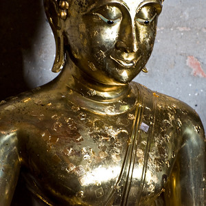 In one of the temples was a small Buddha image. This was perhaps 3 feet tall. It is easy to see where people have bought small squares of gold leaf and rubbed the gold onto the image. And easier still to see it in close up.