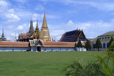 """The Grand Palace is an """"inner city"""" landmark containing multiple buildings detailed with highly decorative architecture. Also situated in the Grand Palace enclave is the Royal Thai Decorations and Coin Pavilion which features royal regalia, medals and coins dating to the early 11th century.  The Grand Palace in the background with public grounds in the foreground. This is the view from the front entrance to the palace enclave."""