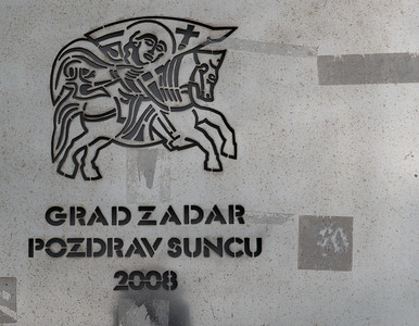"This was a plaque along the waterfront. In Croatian it translates to: ""City of Zadar - Greetings to the Sun."" It was near a neat astronomical park with representations of the planets, the zodiac set in the paving."