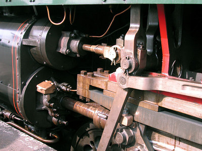 Much of the interest of the locomotive itself is in the mechanisms of locomotion. This is the steam piston which drives the wheels which ultimately drive the train.