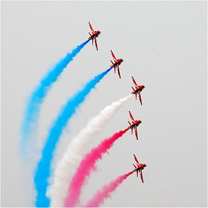 """Royal Air force Aerobatic Team (RAFAT) is called the Red Arrows. This is the British answer to the Canadian Snowbirds, the US Blue Angels and Thunderbirds, the Australian Roulettes, the Russian Knights, the Italian Frecce Tricolori,  and the French La Patrouille de France. They fly the Hawk; an 18,000 lb., 645 mph, single engine  intermediate jet trainer. Here's a link to the Red Arrows official web site: http://www.raf.mod.uk/reds/  Because of the low clouds and weather, they performed their """"low show."""" It was entertaining but less dramatic than their high show."""