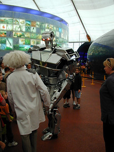 Which is scarier, the robot wandering among the crowd, or the lady with white frizzy hair?