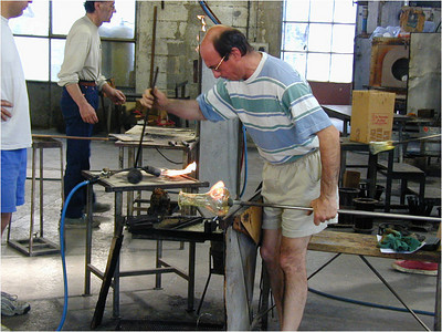 Here a glass artist attached a glob of molten glass to the side of the pitcher and is getting ready blow it into a long thin pour spout. There were several artists working and each tended to specialize in one step of the fabrication of one kind of piece.