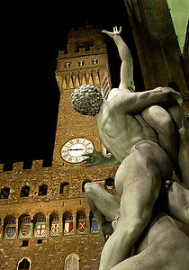 "This photo was taken one night of the Palazzo Vechio (background) and the 1583 sculpture ""Rape of the Sabine Woman"" by Giambologna (foreground). For my money, this sculpture is among the top 5 in Florence. This sculpture was an entrance examination of sorts. Giambologna wanted to enter the city's community of sculpters and was given the task of completing a sculpture that would fit perfectly in a cylinder. This is the result. The title was given later and does not refer to rape in the 21st century context. Rather at the time, ""Raptus"" was more closely associated with theft or abduction. It was not necessarily a sexual crime, or even a crime against the woman, but rather it was a property crime committed against her husband or father. In the statue, the Sabine's father is struggling with a Roman abductor, trying to save his daughter."