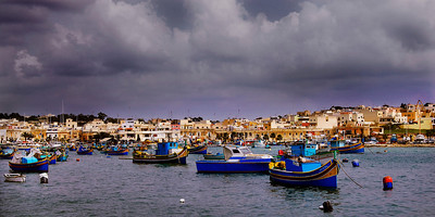 MarsaXlokk: On our second full day on Malta, we took the bus to MarsaXlokk, a small fishing village on the east end of the island country.  The weather was unsettled but it remained warm and we were never rained on. Although picturesque, there's little to see or do in MarsaXlokk. We wandered the waterfront, watched fishermen maintaining their boats and their nets. We hiked around the point (a few miles) and back. It became clear we were here too early ... too early in the day, too early in the season. MarsaXlokk wasn't ready for us. Waiting for the bus back, I had a cup of coffee and Dan had a cup of tea, The coffee was arguably the worst I've ever had ... the color and temperature of well used dishwater. I had a couple of sips and left the remains. But it was a nice day. It didn't spoil my mood.
