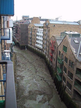 D0003.JPG - 25/05/01 4:19pm   This is the view looking North from the balcony at Flat 81, 8 Shad Thames, London.  The canal here runs off the Thames River.  The buildings you see as well as the one we were staying in are all old warehouses that were used years ago.  Vanessa tells me that the building we were in which is called St Saviour's Wharf, was used as a spice loading dock.  You can see the lifting winch attached to the buildings on the right.  It was low tide when this picture was taken.  Luckily we were up 6 floors so we didn't get any of the smell from below.  I was sure that if I was to stay there longer eventually I would have seen a body wash up.
