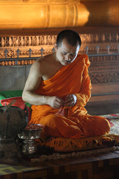 monk giving blessings inside cave of reclining bhudda