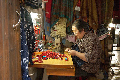 Woman sewing little shoes to sell.