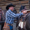 Dustin adjusts his horse saddle.