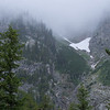 A shrinking glacier, surrounded by fog on a cold, rainy day.