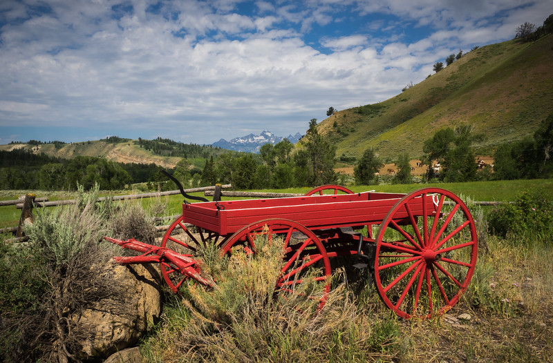 "The old red wagon ,  with the peaks of  the Grand Tetons visible over the hills, hearkens back to the days when horses supplied the power to move the ""vehicle."""