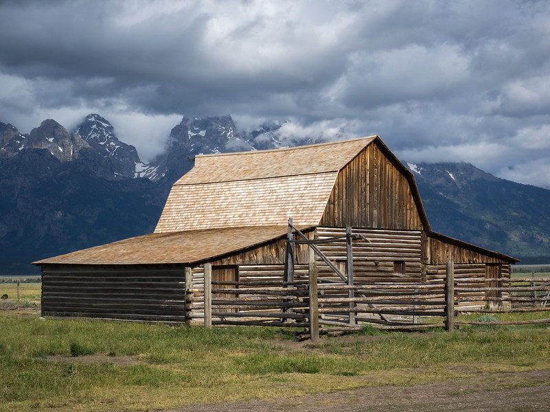 This is one of two structures known as the Mormon Barns.  Storm clouds are brewing.
