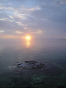 The sun rising over Yellowstone Lake with Fishing Geyser in the foreground in Yellowstone National Park. Before it was protected, fishermen would catch a fish in the lake, and then drop the fish in the geyser to cook it.  All without removing it from the fishing line.