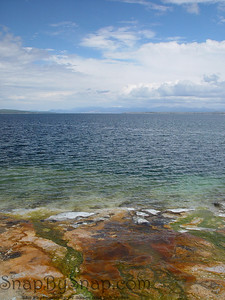 The colorful shoreline of West Thumb Geyser Basin in Yellowstone National Park connects with the cold water of Yellowstone lake.