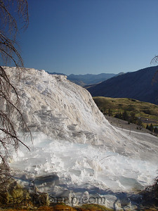 This is Canary Spring at Mammoth Hot Springs in Yellowstone National Park.  This image was taken less then 24 hours after an earthquake that diverted the flow of the hot spring from a wide terrace to a thing stream.    3 years earlier, I remember sitting on a bench on the board walk in the morning and enjoying a natural steam bath.  After the earthquake, it is only a memory.