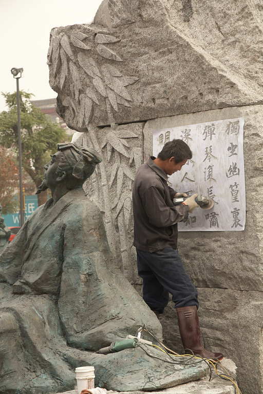 A worker carves Chinese characters into the display.