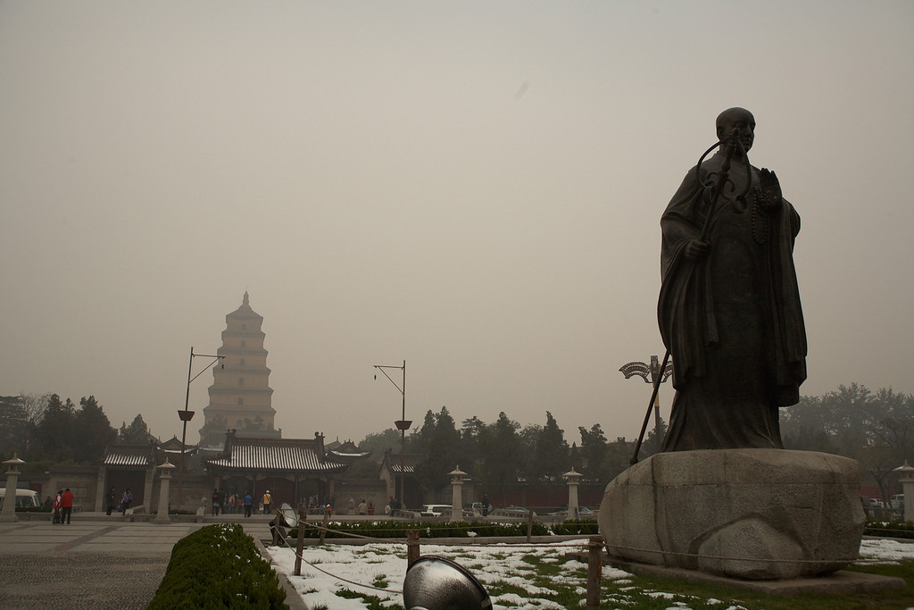 The statue is the monk Xuan Zang. He traveled to India to read the original Buddhist scriptures. He translated the Buddhist scriptures from their original Sanskrit and brought them back to China. His translations are stored in the Giant Wild Goose Pagoda, the tall tower in the background. This pagoda is on the grounds of the Da Ci'en Temple. Both were built in the mid 600s.
