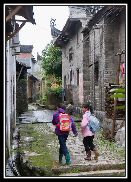 Girls walking home from school along alley...