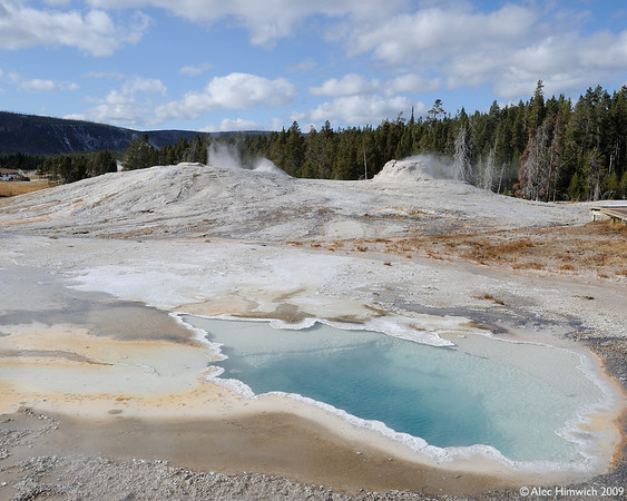 This photo from the Old Faithful Geyser Basin, gives you a little idea of the other-worldly landscape and colors.  You can see steaming geysers in the background and the unusual colors in the pond generated by heat-loving algae and bacteria.