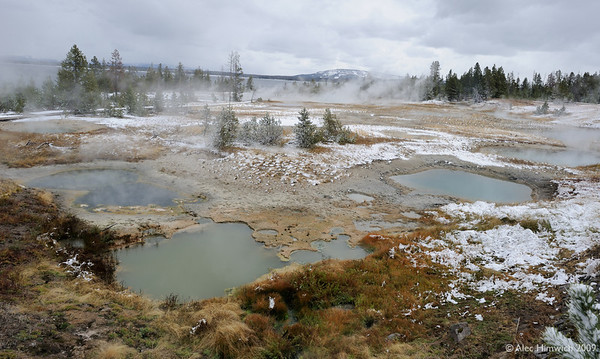 Here are some of the small ponds at the West Thumb Geyser Basin.  We did not see any actual geysers here, but we did see mud pots, these ponds and interesting colors.<br /> <br /> You can see Yellowstone Lake in the background.
