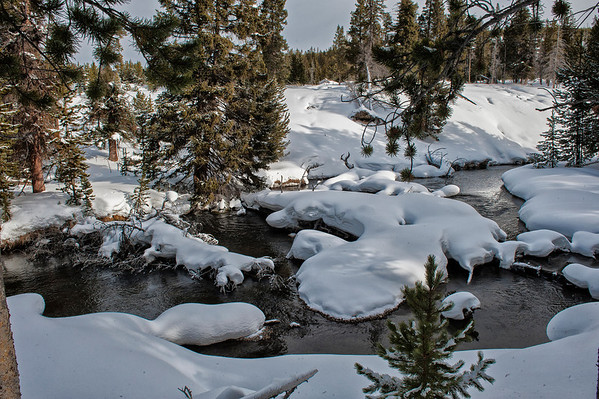 A creek warmed by the volcanic hotspot, threads its way through snow covered banks and debris in spite of temperatures occasionally falling near -40 degrees.