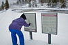 Model Released, Woman Reading Trail Sign, Winter, Old Faithful Area, Yellowstone National Park, Wyoming, USA, North Amercia