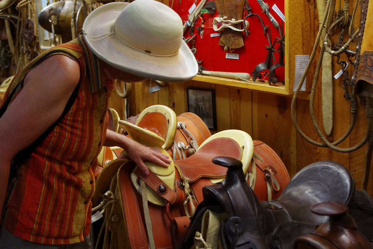 Rita examines one of hundreds (thousands?) of saddles - old and new - King's Saddlery, Sheridan, Wyoming.